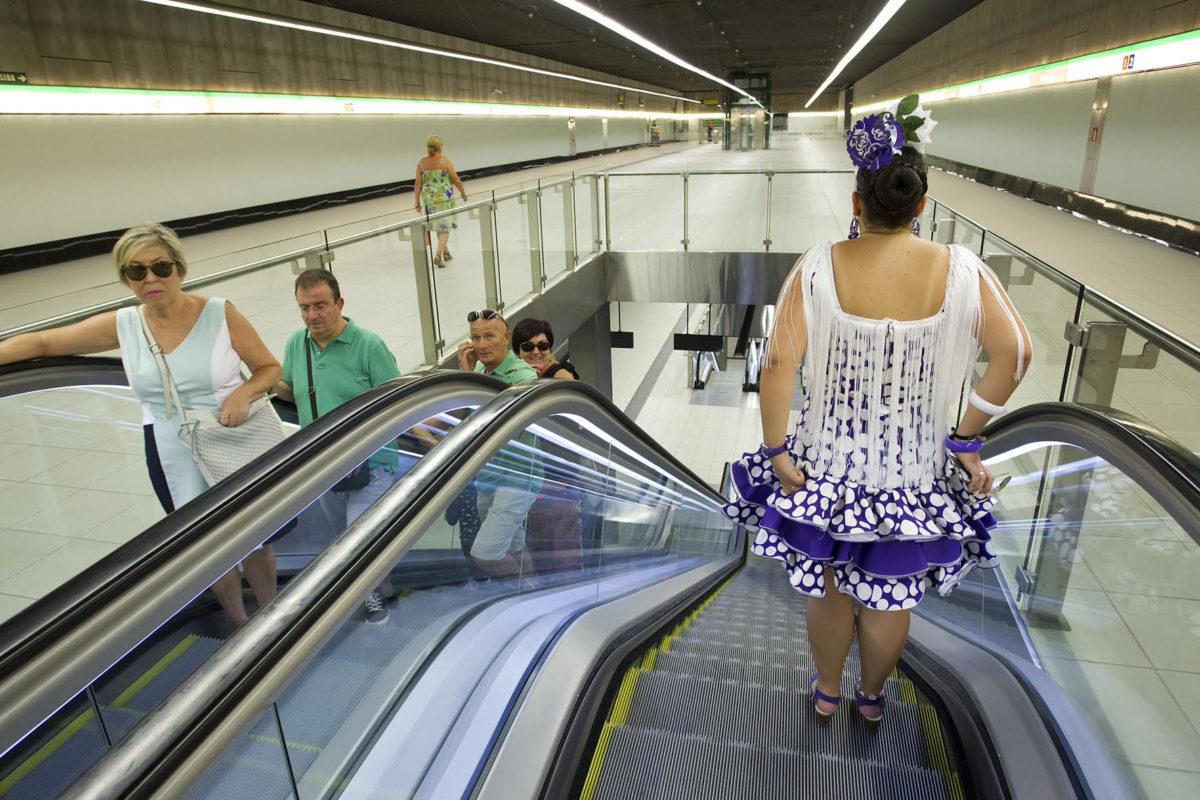 Una mujer vestida con traje regional baja al andén mientras otros usuarios suben las escaleras mecánicas